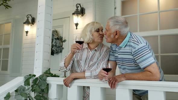 Senior Elderly Caucasian Couple Drinking Wine, Looking Ahead, Making a Kiss in Porch at Home
