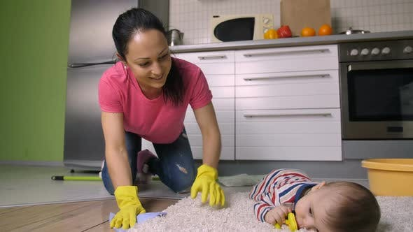 Thumbnail for Latin Mother on Knees Scrubbing Floor with Baby