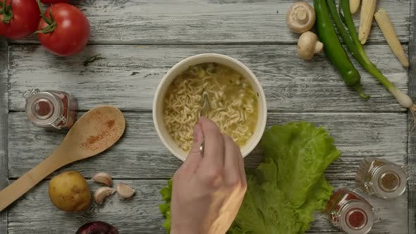 Thumbnail for Crop Cook Mixing Delicious Cheap Noodle Soup with Fork