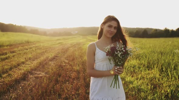 Thumbnail for Young Woman Standing in a Meadow with Bouquet of Wild Flowers on Summer Evening