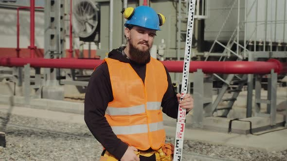 Bearded Engineer Holds Geodetic Pole Posing at Power Station