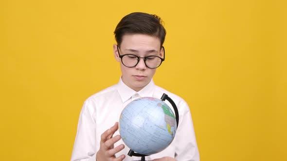 Smart Schoolboy Pointing Finger At Destination On Earth Globe Studio