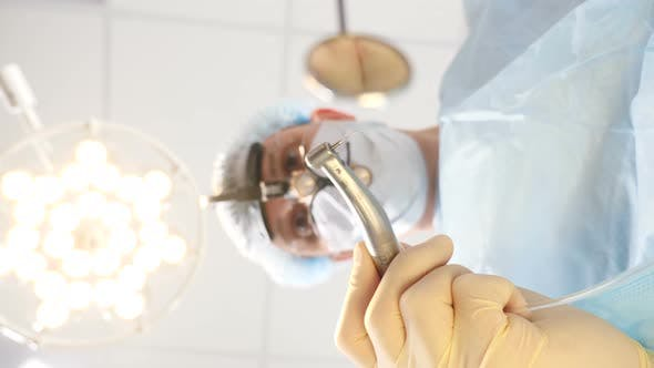 POV of Patient in Dental Clinic. Doctor in White Aseptic Mouth Mask Approaching Patient