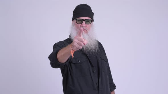 Cover Image for Mature Bearded Hipster Man Looking Serious While Pointing at Camera
