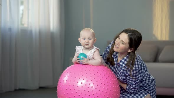 Thumbnail for Happy Mother and Cute Baby Girl Smiling at Camera, Playing With Balls at Home