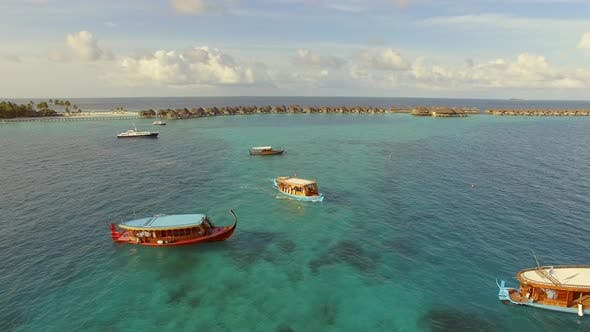 Thumbnail for Aerial view of three traditional boats anchored next to Maldives island.