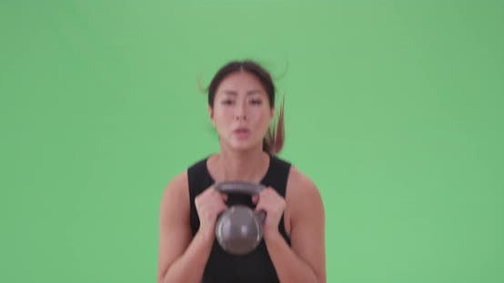 Thumbnail for Asian woman lifts a kettle bell while another woman exercises on green screen