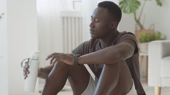 Schwarzer Mann macht Bauchübungen auf dem Boden zu Hause, eine Pause, um Wasser zu trinken