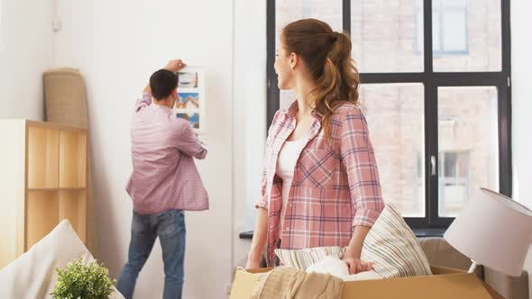 Cover Image for Happy Couple Moving To New Home and Hanging Photo