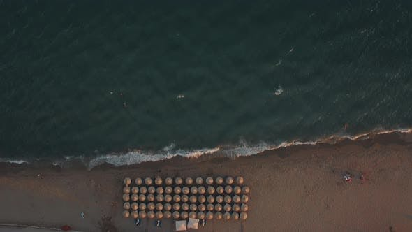 Thumbnail for Aerial Shot of Blue Sea and Sunbeds Under Umbrellas at the Beach