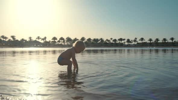 Thumbnail for Sweet Active Toddler Falling Into Seawater at Summer Coastline.