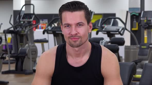 Thumbnail for A Young Fit Man Shows a Thumb Up To the Camera and Nods in a Gym - Closeup