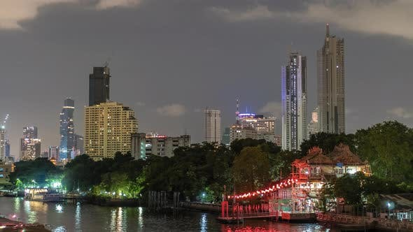 Thumbnail for Timelapse Skyscrapers in Nightfall Downtown and River at Foreground