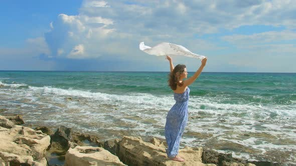 Thumbnail for Woman Standing on Seashore, White Scarf Waving in the Wind. Symbol of Freedom