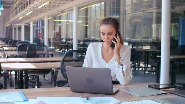 Thumbnail for Businesswoman Typing on Laptop Talking By Mobile