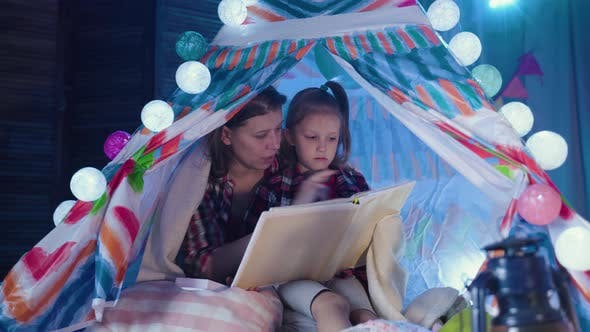 Thumbnail for Family Bedtime. Mom And Child Daughter Reading Book In Tent