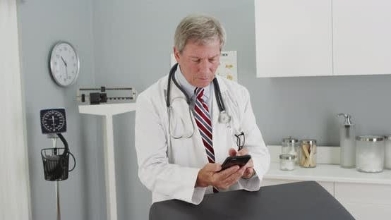 Thumbnail for Senior doctor using smartphone in the office