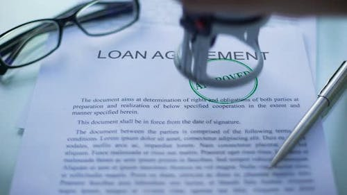 Loan Agreement Approved, Officials Hand Stamping Seal on Business Document