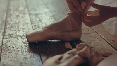 Ballerina Prepares for Performance Ties Ribbons on Pointe