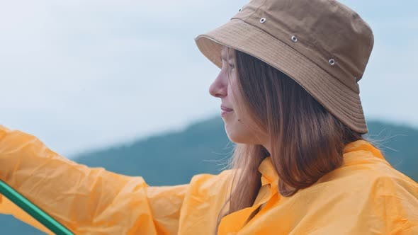 Thumbnail for Lonely Woman in an Orange Raincoat on Fishing