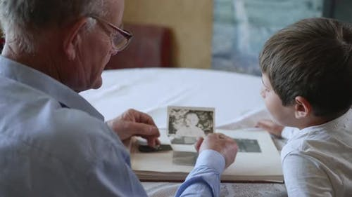 Friendly Grandfather with His Beloved Grandson Shows Photos of Youth Rejoicing in Memories of Youth