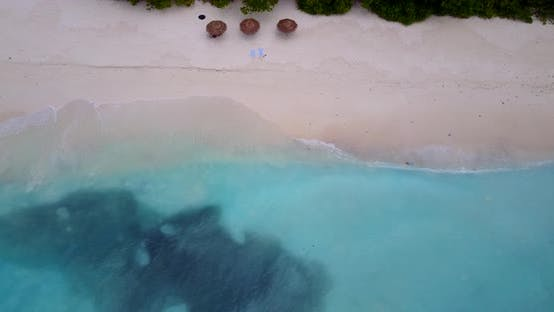 Daytime birds eye clean view of a paradise sunny white sand beach and aqua blue ocean background in