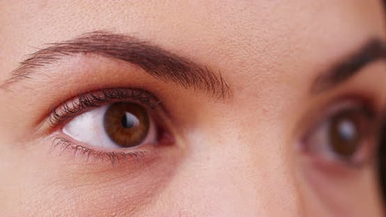 Thumbnail for Extreme close up of female millenial's eyes blinking, looking off camera