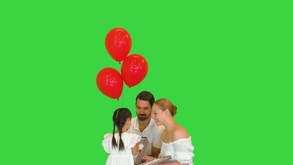 Family Holidays Concept  Parents Give a Present To Happy Little Girl on a Green Screen Chroma Key