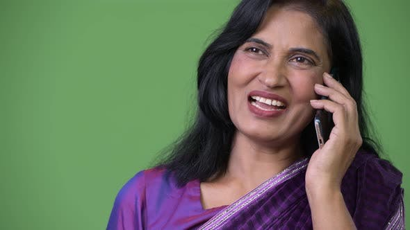 Thumbnail for Close Up Shot of Mature Happy Beautiful Indian Woman Talking on the Phone While Thinking