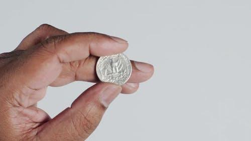 Hand Holds a Quarter