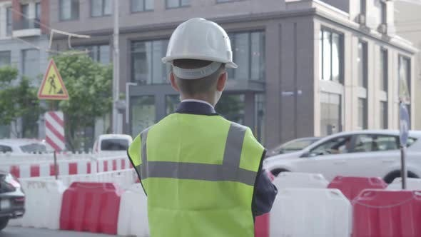 Thumbnail for Little Boy Wearing Business Suit and Safety Equipment and Constructor Helmet Standing on a Busy Road
