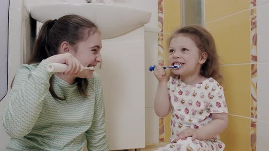 Thumbnail for Little Two Sisters Brushing Their Teeth Intensely in the Bathroom. Close Up