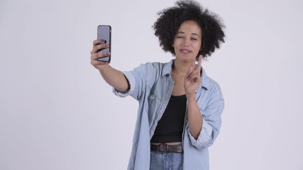 Cover Image for Young Happy African Woman Video Calling and Showing Phone