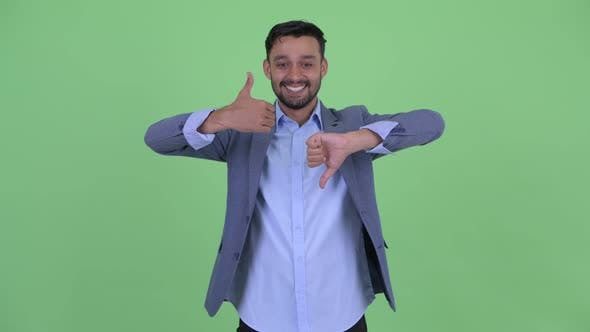 Thumbnail for Happy Young Bearded Persian Businessman Choosing Between Thumbs Up and Thumbs Down