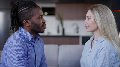 Side View of Loving Interracial Couple Looking at Each Other with Love Sitting on Comfortable Couch