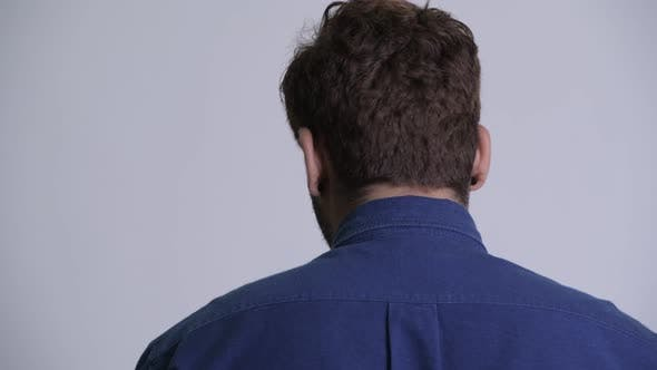 Cover Image for Closeup Rear View of Young Bearded Indian Businessman Looking Back