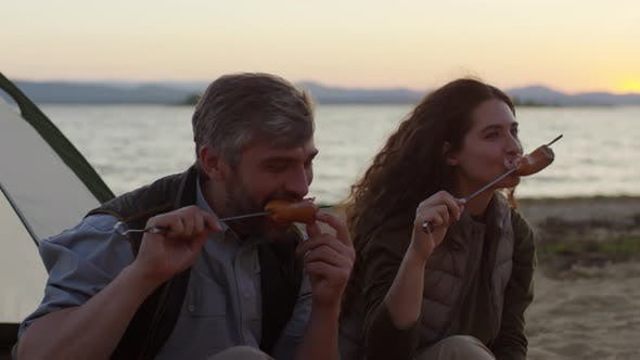 Thumbnail for Couple Eating Sausages on Sticks at Campsite on Beach