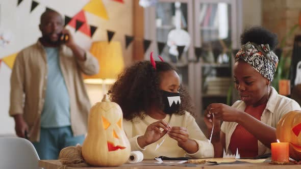 Mom and Daughter Making Halloween Face Masks with Vampire Teeth