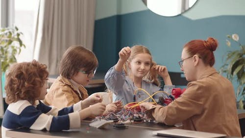Young Female Tutor and Three School Kids Constructing Robots