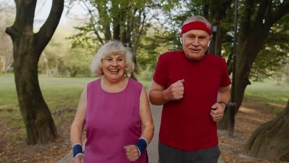 Thumbnail for Active Senior Elderly Couple Doing Cardio Morning Exercise Workout. Man, Woman Running in City Park.