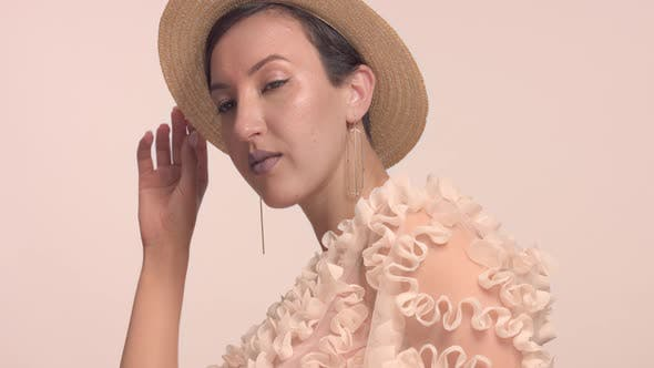 Thumbnail for a Young Moroccan Woman Wears a Hat in the Studio and Monochrome Makeup
