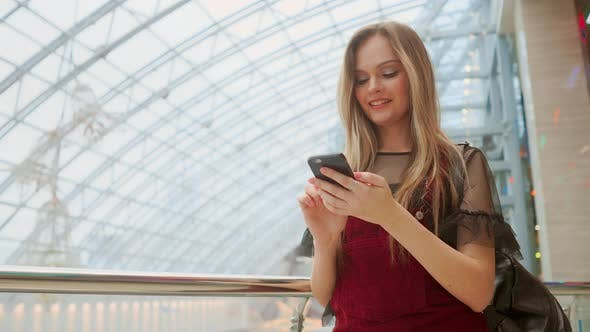 Cover Image for Girl Use Mobile Phone, Blur Image of Inside the Mall As Background