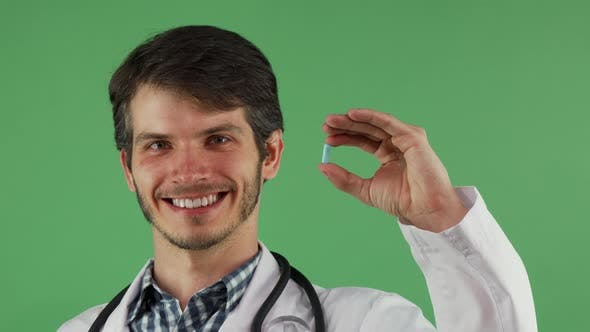 Thumbnail for Cheerful Male Doctor Smiling Holding Blue Pill on Green Background