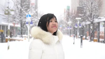 Portrait Of Beautiful Asian Girl Enjoying Snowfall