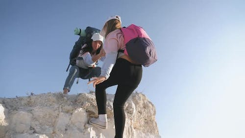 Girl Helps Her Friend Climb Up the Last Section of Mountain. Tourists with Backpacks Help Each Other
