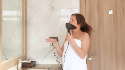 Delighted Young Woman Dances and Sings Into Hairdryer