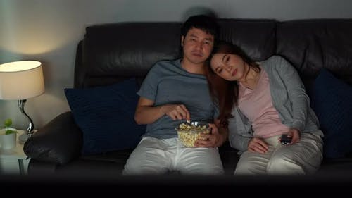young couple watching TV movie on sofa at night