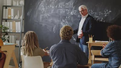 Professor Explaining Formulas on Chalkboard to Students