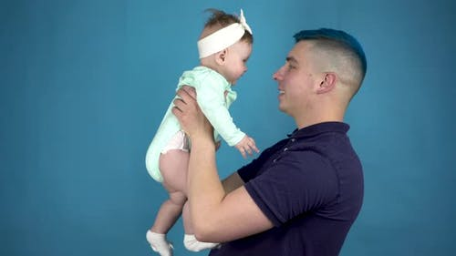 A Young Father with Blue Hair Holds a Baby in His Arms. Alternative Man with a Child Look at the