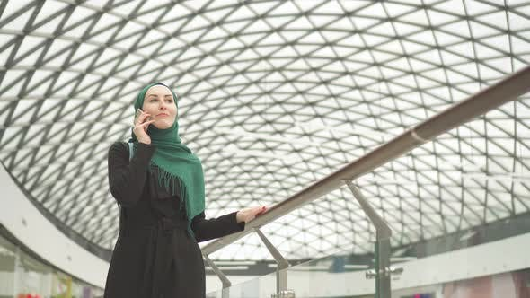 Pretty Muslim Woman in a Hijab with a Backpack Goes To the Shopping Center and Talks on the Phone